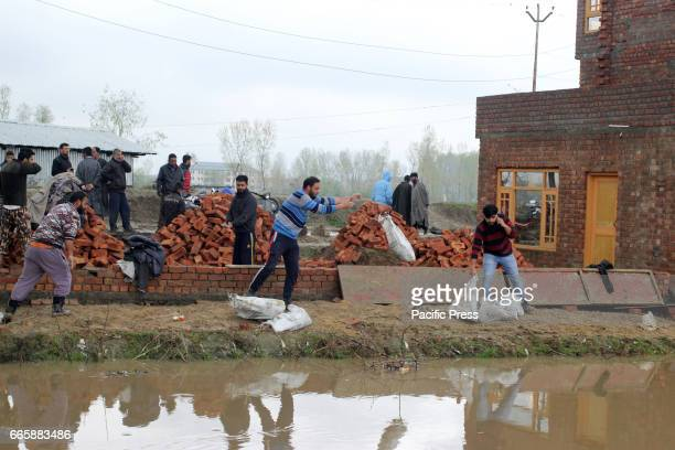 People place sand bags in Bemina area of Srinagar district to stop overflow of the water from entering residential houses as water level increases in...
