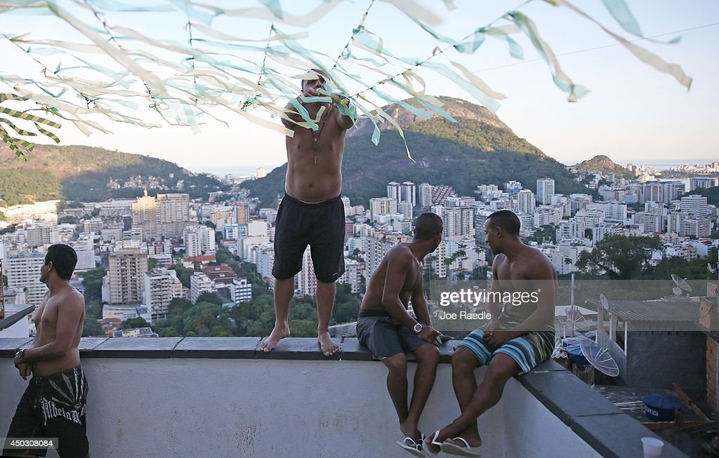 People place streamers above a patio, in a 'favela' called Santa Marta, in preparation for when the Brazilian soccer team plays during the World Cup on June 8, 2014 in Rio de Janeiro, Brazil. Brazil continues to prepare to host the World Cup which starts on June 12th and runs through July 13th.
