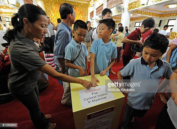 People place their donation in a box for cyclone victims in Myanmar after a prayer at the Burmese Buddhist Temple in Singapore on May 11 2008 China's...
