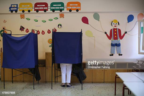 People place their referendum votes in the ballot box at a school in the suburbs of Athens on July 5 2015 in Athens Greece The people of Greece are...