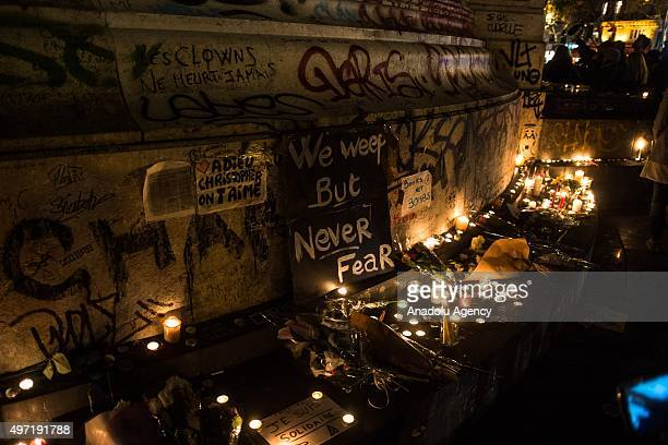 People place tributes to the victims of the attacks in and around Paris at the Place de la Republique square in Paris on November 14 2015 At least...