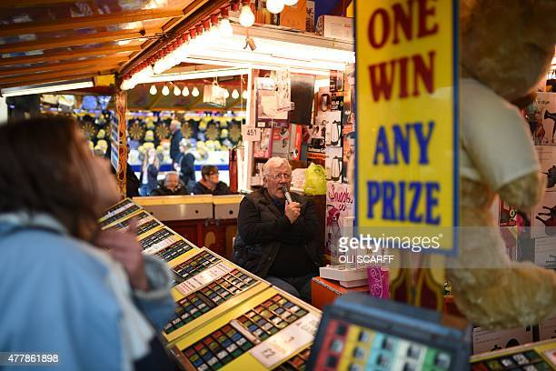 People play a game of bingo in a stall at The Hoppings fun fair believed to be one of the largest travelling funfairs in Europe on its opening day in...