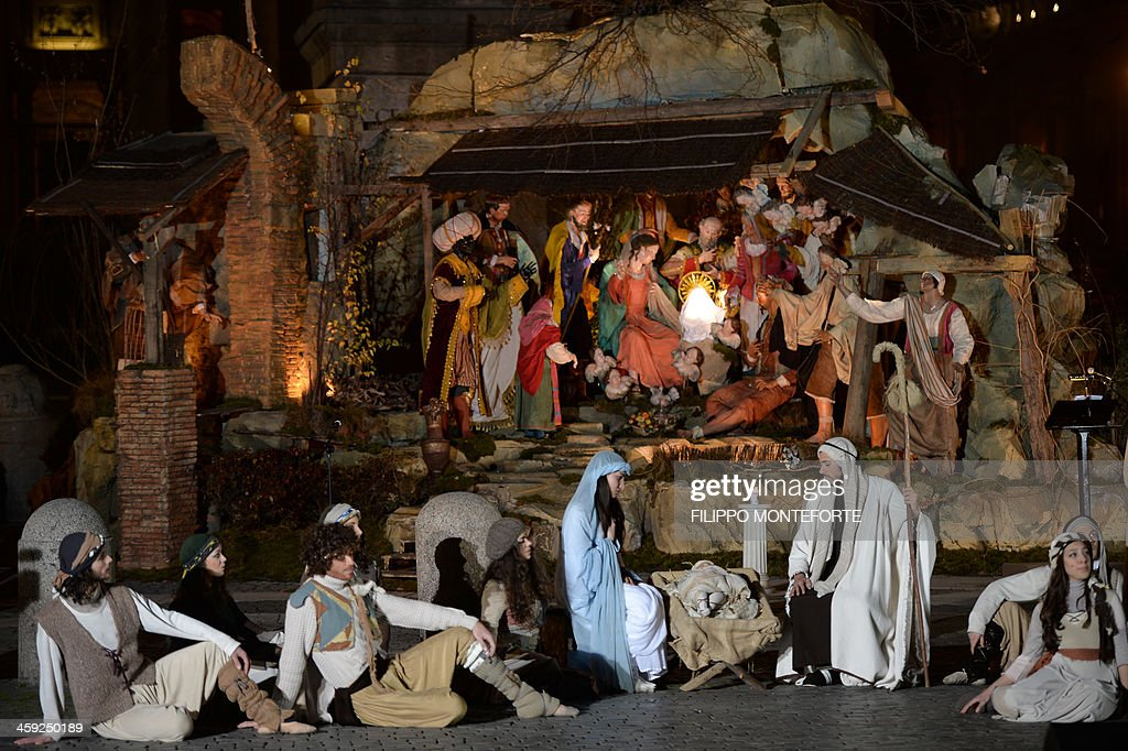People play a nativity scene during the unveiling ceremony of the crib in St Peter's Square at the Vatican on December 24 2013 Pope Francis visited...