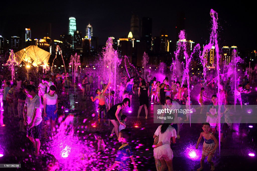 People play and enjoy the water in a fountain square on August 4, 2013 in Chongqing, China. Chongqing is a major city in southwest China and became the municipality was created on 14 March 1997. It known as a 'Mountain City' and 'River City' was constructed on the mountain and along the Yangtze River.
