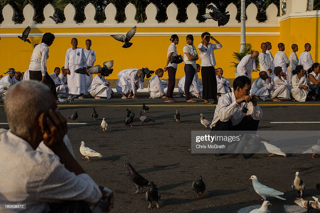 People play and feed pigeons as they wait outside the Royal Palace before being allowed to enter the cremation site to pay final respects to former King Norodom Sihanouk on February 2, 2013 in Phnom Penh, Cambodia. The former kings coffin was transported to the cremation site yesterday after being paraded through the capital in a lavish funeral procession. The cremation will take place on Monday the 4th of February, the funeral pyre will be lit by his wife and son King Norodom Sihamoni.