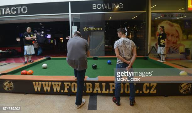 People play and watch a footballpool match on April 28 2017 in Prague Footballpool is a combination of football and pool the sport uses inflatable...