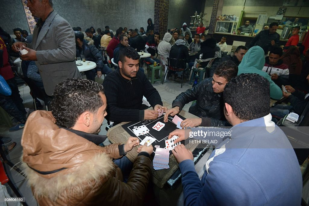 People play at cards at a cyber-cafe in the town of Ben Guerdane, Tunisia, near the border with Libya, on February 5, 2016. Tunisia said on February 4 that it was lifting a nationwide nighttime curfew imposed last month after the worst social unrest witnessed in the country since its 2011 revolution. / AFP / FETHI