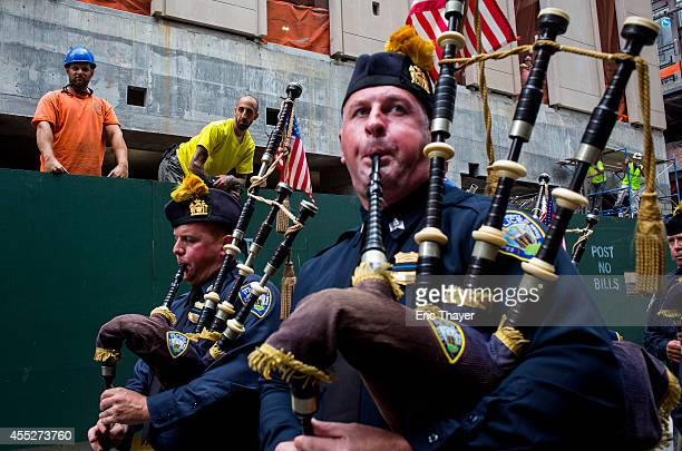 People play bagpipes before an interfaith remembrance service at St Peter's Roman Catholic Church September 11 2014 in New York CIty This year marks...