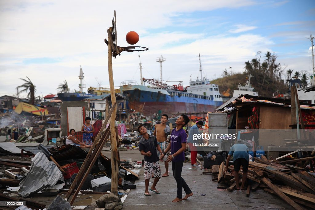 People play basketball with a make shift hoop near a tanker which ran a ground and came to rest amongst debris in Tacloban on November 17 2013 in...