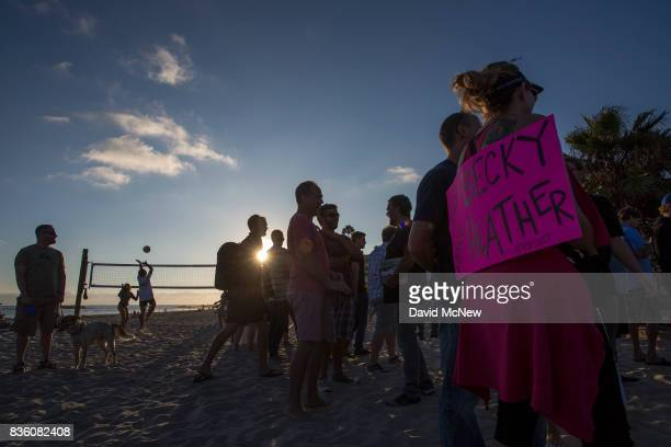 People play beach volleyball near counter demonstrators during an 'America First' demonstration on August 20 2017 in Laguna Beach California...