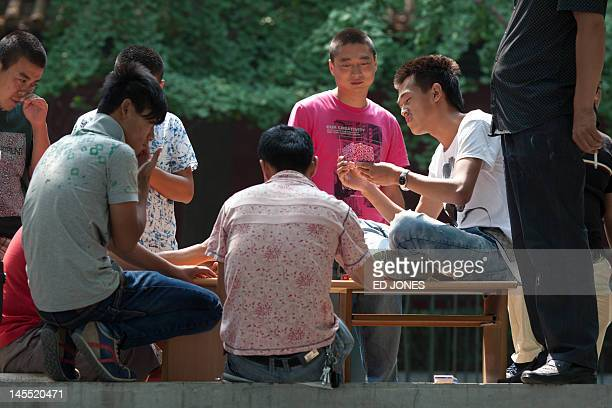 People play cards on a street in Beijing on June 1 2012 China's exportdriven economy has begun to slow this year with growth falling to 81 percent in...