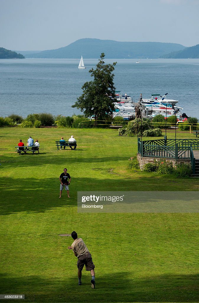 People play catch at Lakefront Park on the south end of Otsego Lake in Cooperstown New York US on Saturday July 26 2014 President Obama during a...