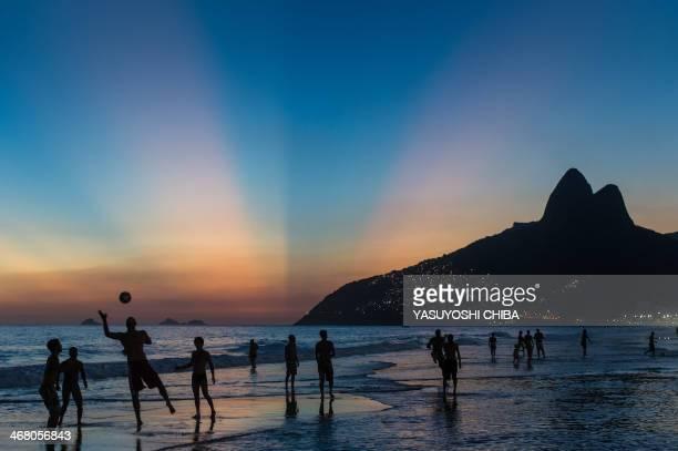 People play football at Ipanema beach at sunset in Rio de Janeiro Brazil on January 29 2014
