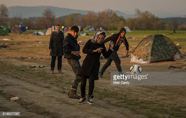 People play football at the Idomeni refugee camp on the Greek Macedonia border on March 19 2016 in Idomeni Greece Thousands of migrants remain...