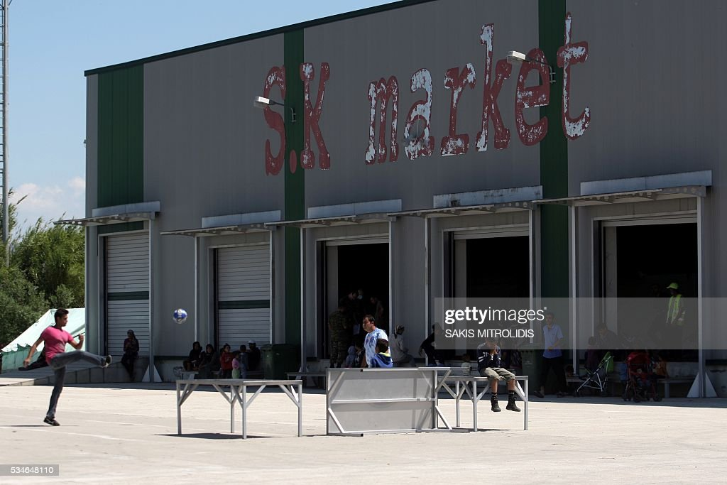 People play football inside a new camp for refugees and migrants set in an abandoned factory in Sindos, a west suburb of Thessaloniki on 27 May, 2016. The squalid Idomeni refugee camp in northern Greece which became a symbol of Europe's migrant crisis has been fully evacuated, police said Thursday, as another 30 died crossing the Mediterranean. In the space of three days, police transferred about 4,000 migrants by bus from Idomeni to newly created camps in the industrial outskirts of Greece's second city Thessaloniki. / AFP / SAKIS