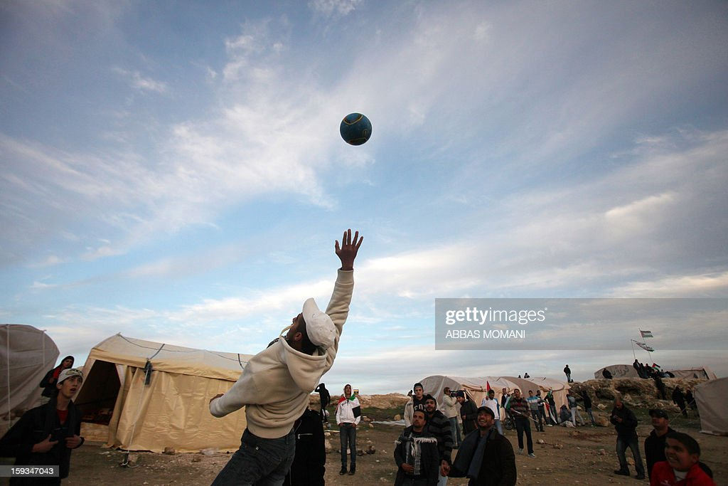 People play football near tents that Palestinian activists set up in an 'outpost' named Bab al-Shams ('Gate of the Sun') between Jerusalem and the Jewish settlement of Maale Adumim in the Israeli-occupied West Bank, in an area where Israel has vowed to build new settler homes, on January 12, 2013. The Israeli occupation administration gave Palestinian activists an ultimatum to quit the protest camp in part of the West Bank, but hours after the deadline passed, there was no sign of any Israeli move to evict the protesters.