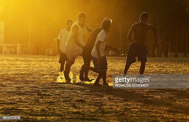 People play football on a beach of Santos on June 30 during the 2014 FIFA World Cup football tournament in Brazil AFP PHOTO / RONALDO SCHEMIDT