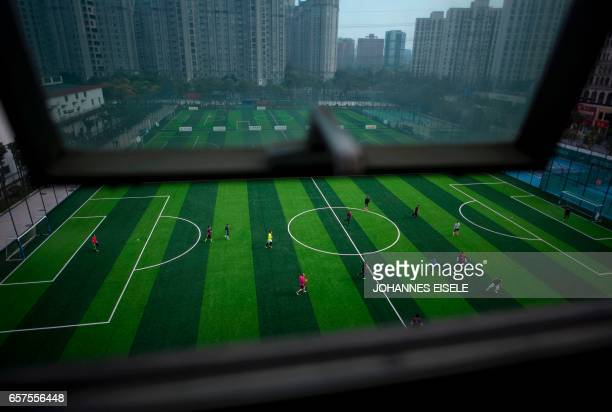 TOPSHOT People play football on a grey afternoon in Shanghai on March 25 2017 / AFP PHOTO / Johannes EISELE