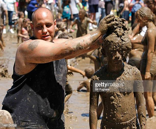 People play in a giant lake of mud at the 25th annual 'Mud Day' July 10 2012 in Westland Michigan The event which features a 75' by 150' pit filled...