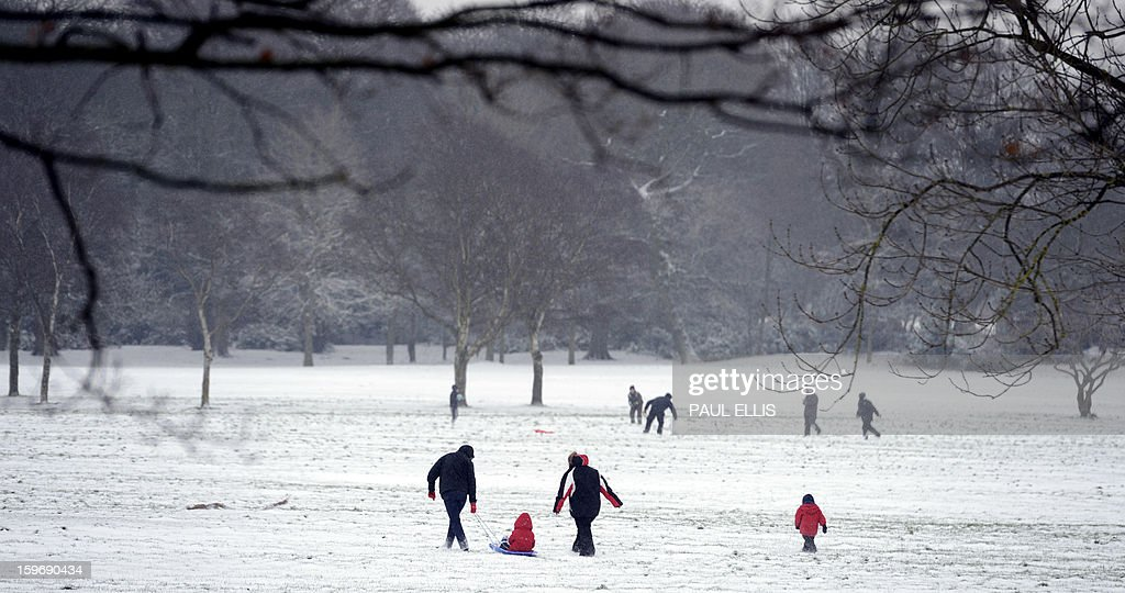 People play in snow in Birkenhead park, north-west England, on January 18, 2013. Snow swept across Britain, forcing airports to cancel dozens of flights and more than 2,000 schools to close.