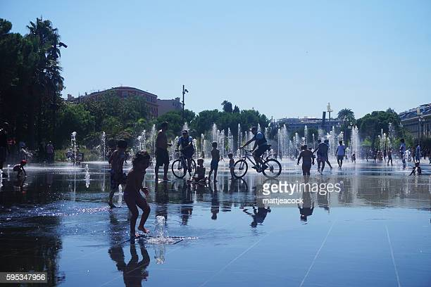 People play in the fountains in Nice, France