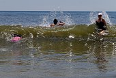People play in the waves at Rockaway Beach on July 26 2016 in New York City A heat wave continues with temperatures expected to stay in the 90's...