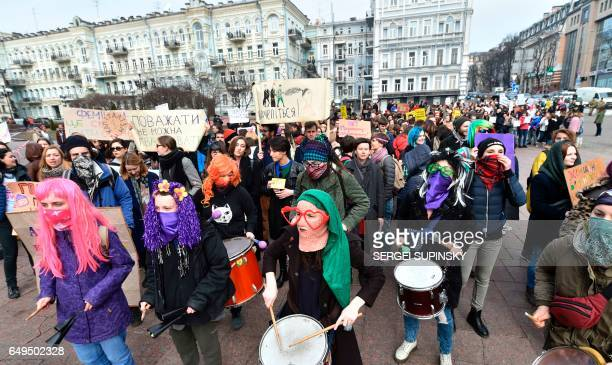People play instruments carry placards and shout slogans during a march as part of International Women's Day on March 8 2017 in Kiev / AFP PHOTO /...