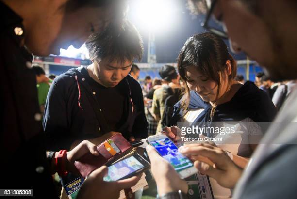 People play Nintendo Co's Pokemon Go augmented reality game on their smartphones during the Pokemon Go Stadium event at Yokohama Stadium that was...