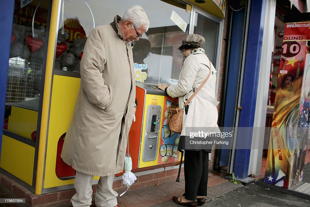 People play on machines outside an amusement arcade on August 5, 2013 in Rhyl, Wales. The think tank The Centre for Social Justice (CSJ) has today said that some British seaside towns such as Rhyl in North Wales were becoming 'dumping grounds' for vulnerable people. The report 'Turning the Tide' has monitored conditions in five seaside towns, Rhyl in Denbighshire, Margate in Kent, Clacton-on-Sea in Essex, Blackpool in Lancashire and Great Yarmouth in Norfolk. In one area of Rhyl, over 66% of working-age people were found to be dependent on out-of-work benefits.