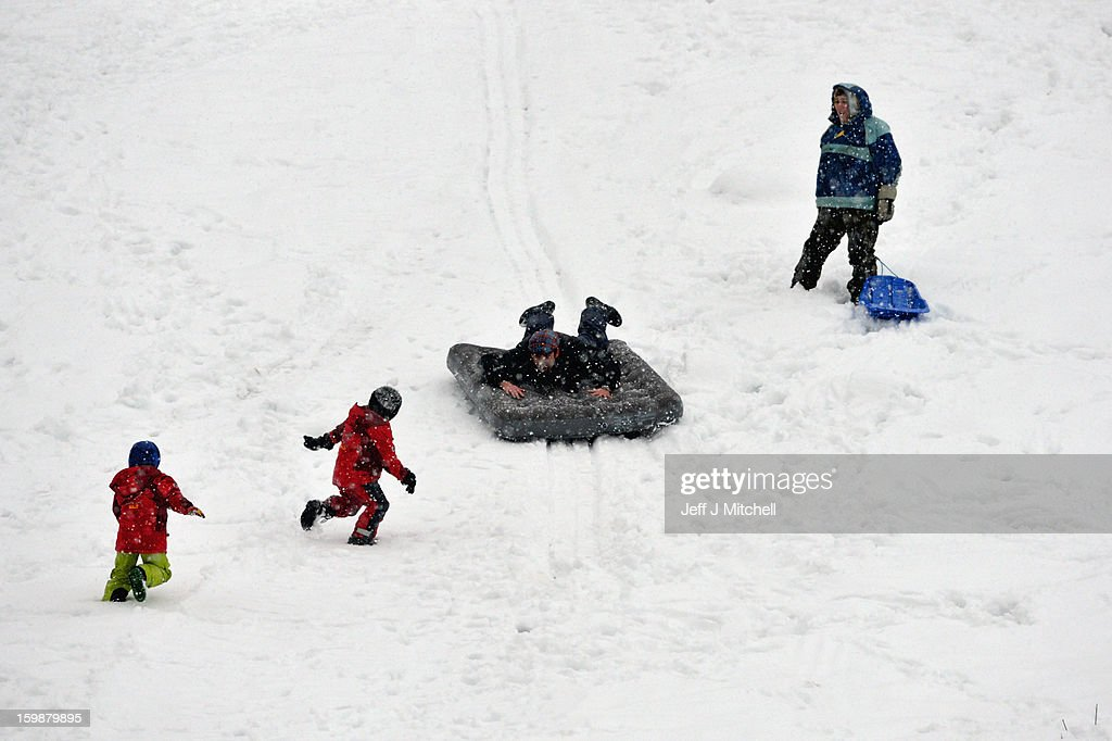 People play on sledges in the snow on January 22, 2013 in Dunkeld, United Kingdom.The Met Office has issued a red weather warning for parts of the Uk and advising against all non-essential travel as up to 30cm of snow is expected to fall in some areas today. The adverse weather has closed nearly 5,000 schools and caused many airports to cancel flights.