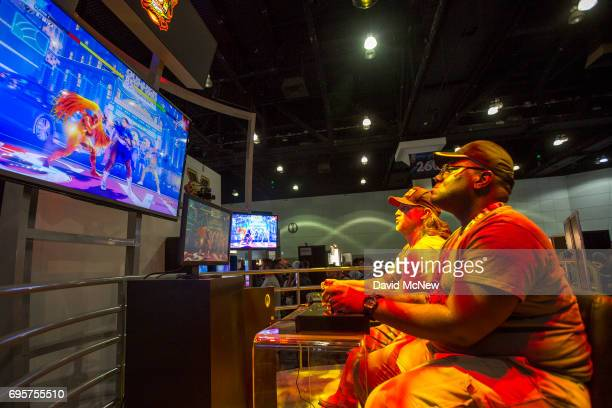 People play Ultra Street Fighter II The Final Challengers on opening day of the Electronic Entertainment Expo at the Los Angeles Convention Center on...