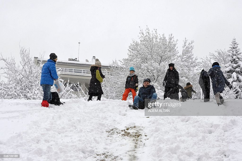 People play under the snow as a man slides down a hill covered with snow in Ankara on February 6, 2016. / AFP / ADEM ALTAN