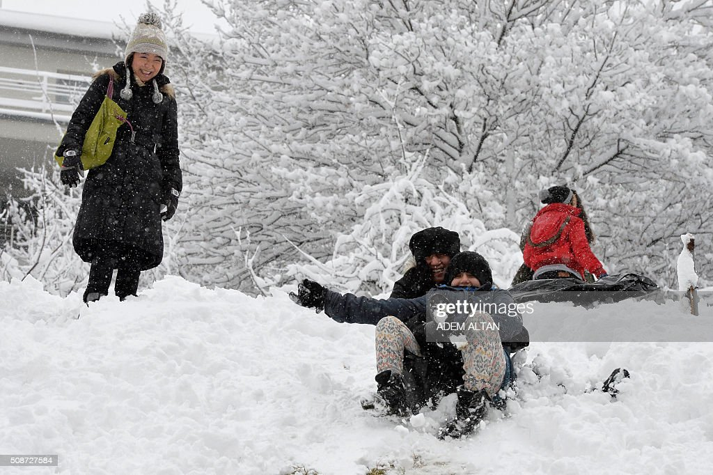 People play under the snow as they slide down a hill covered with snow in Ankara on February 6, 2016. / AFP / ADEM ALTAN