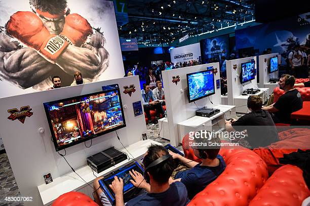 People play video games at the Sony Playstation stand at the Gamescom 2015 gaming trade fair during the media day on August 5 2015 in Cologne Germany...