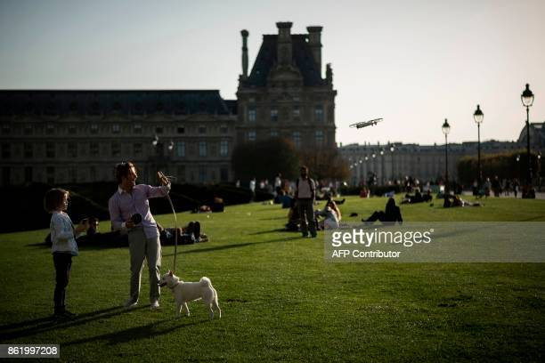 People play with a drone at the Tuileries Garden on October 16 2017 in Paris / AFP PHOTO / Lionel BONAVENTURE
