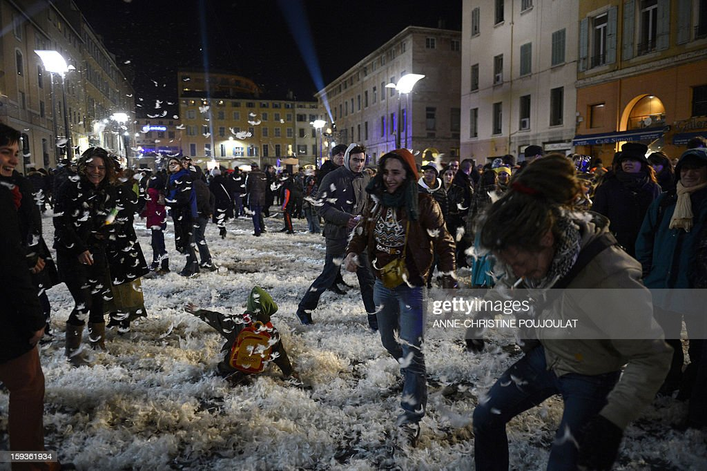 People play with feathers after the Studio de Cirque company show 'Place des Anges' at the Cours d'Estienne d'Orves on January 12, 2013 in Marseille, one of the events marking the launching of festivities for the Marseille-Provence 2013 European Capital of Culture. The event marks the start of a year of cultural renaissance in France's second-largest metropolitan area.