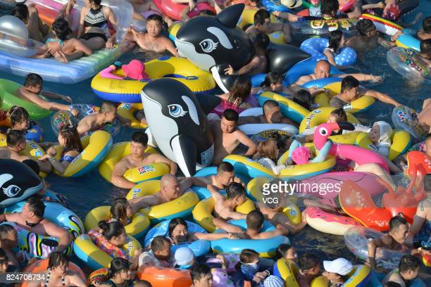People play with inflatable rings and toys at a water park to avoid heat on July 30 2017 in Fushun Liaoning Province of China As the temperature...