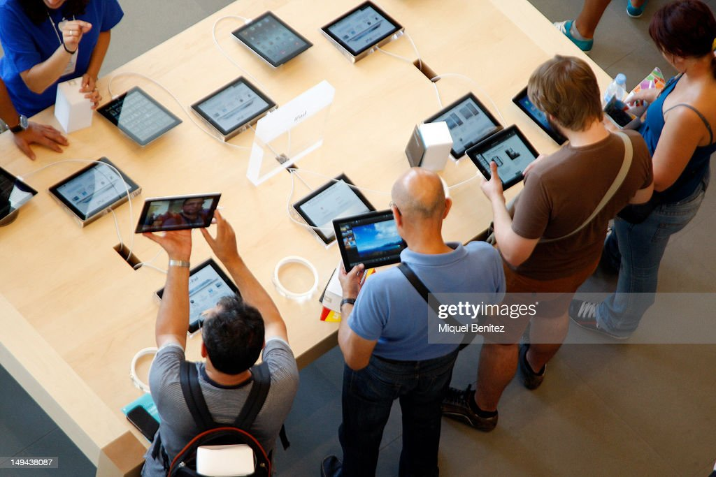 People play with iPad as they attend the opening of Apple's New Barcelona Store in Passeig de Gracia on July 28, 2012 in Barcelona, Spain.
