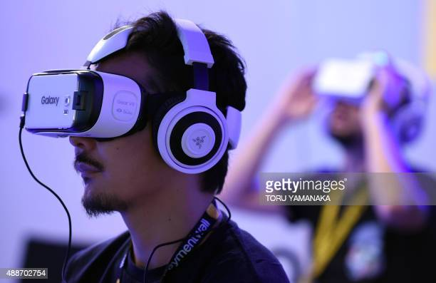 People play with virtual reality head gear 'Gear VR' of Oculus during the Tokyo Game Show in Chiba a suburb of Tokyo on September 17 2015 The Tokyo...