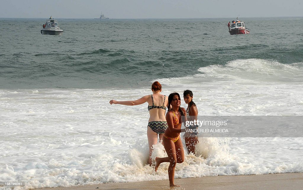People play with water in the coast as a ship of the Brazilian Navy (L) and a firefighter ship look for a fallen helicoper in Copacabana beach, Rio de Janeiro, Brazil on December 29, 2012. A firefighter helicopter fell on the sea as it rescued a bather. The man and the three crew members survived.