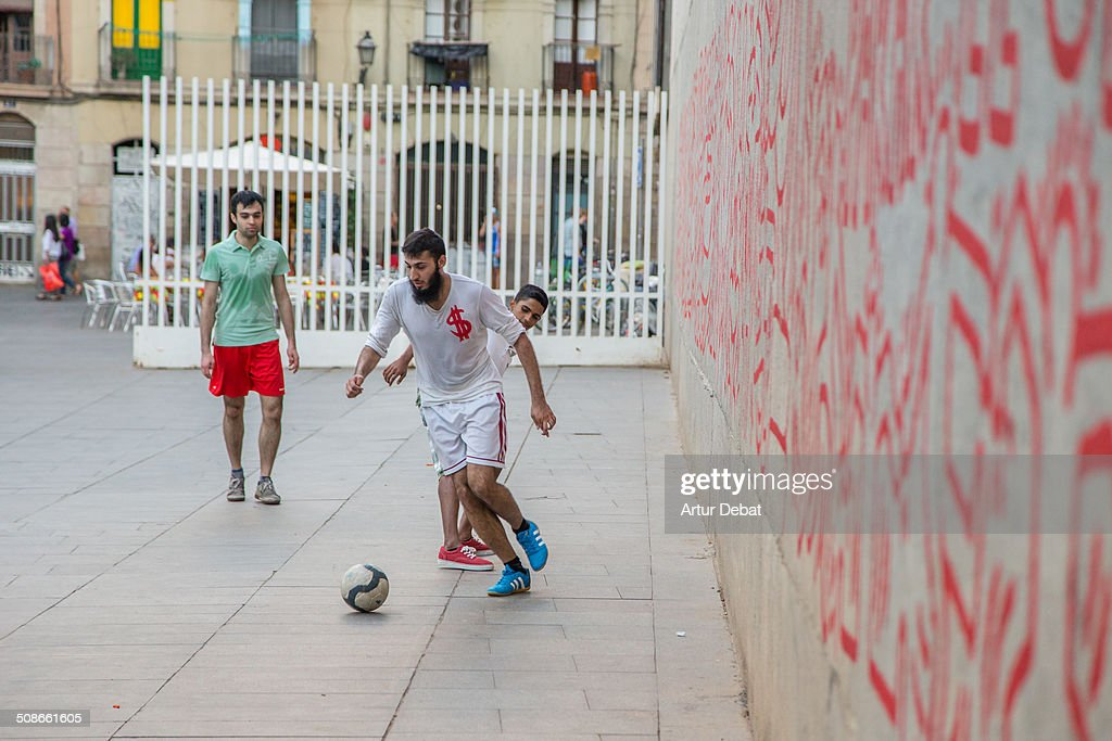 People playing a spontaneous football match adapting the city to the court with big doors like football goals.