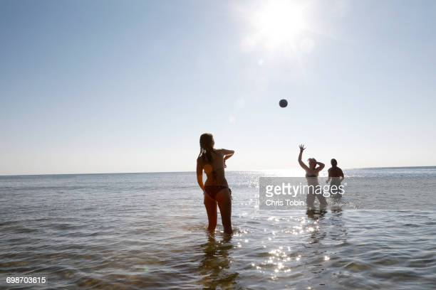 People playing ball in water at beach