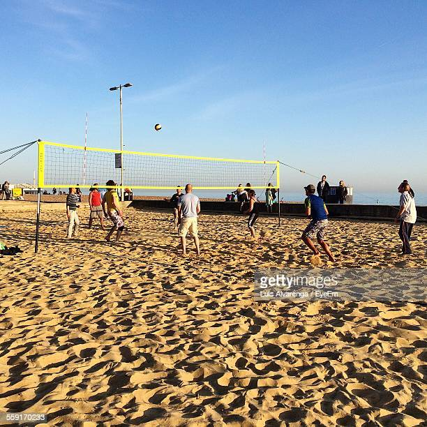 People Playing Beach Volleyball Against Sky During Sunny Day