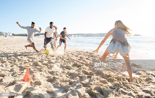People playing football at the beach