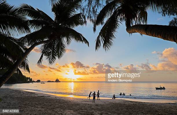 People playing in the sunset on a tropical beach