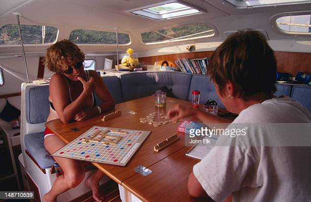 People playing scrabble in cabin aboard bare boat charter yacht.
