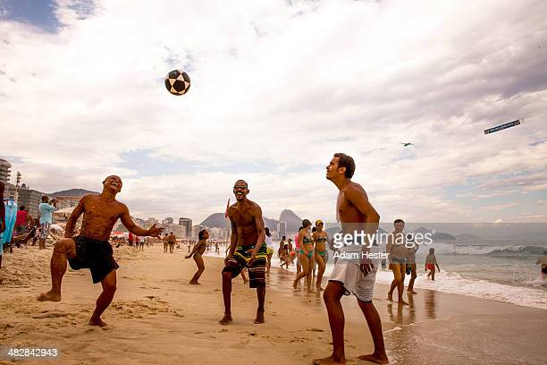 People playing soccer outside on Ipanema Beach.