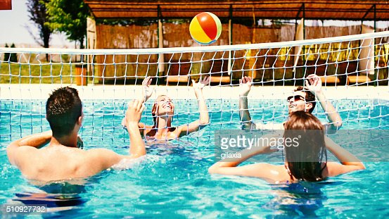 People playing volleybay in swimming pool and having beers.