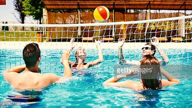 Personnes jouant volleybay dans la piscine et avoir de bières.