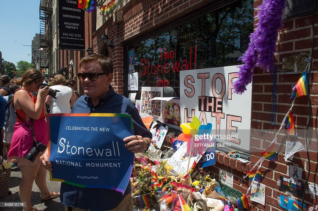 People pose and photograph the Stonewall Inn as Mayor Bill de Blasio joins elected officials, advocates and New Yorkers in designating Stonewall Inn a National Monument, on June 27, 2016 in New York. / AFP / Bryan R. Smith